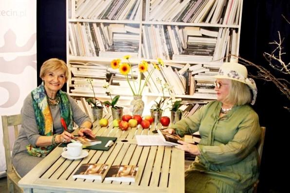 Autorka wraz zprowadzącą spotkanie siedzą przy stole, nanim wazon zkwiatami, jabłka