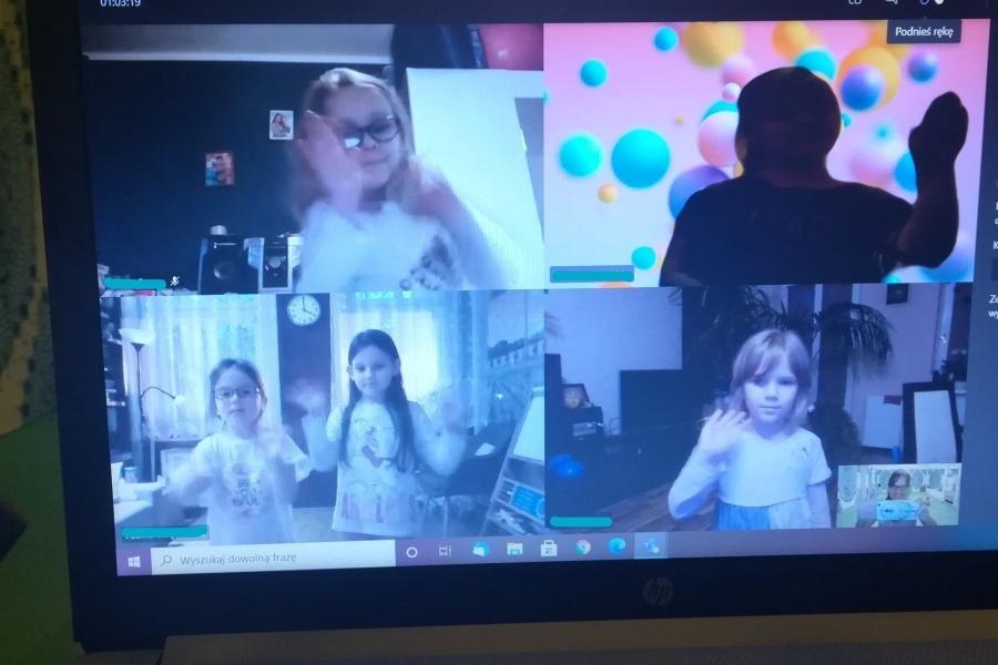 Na zdjęciu monitora komputera w podzielonych okienkach sześć dziewcząt stoi w pozie tanecznej zjedna ręka wyprostowana do boku, a druga ugiętą w łokciu.