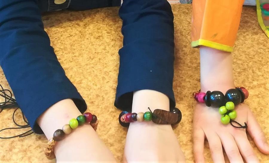 Widoczne trzy dłonie zkolorowymi bransoletkami wykonanymi zdrewnianych koralików.
