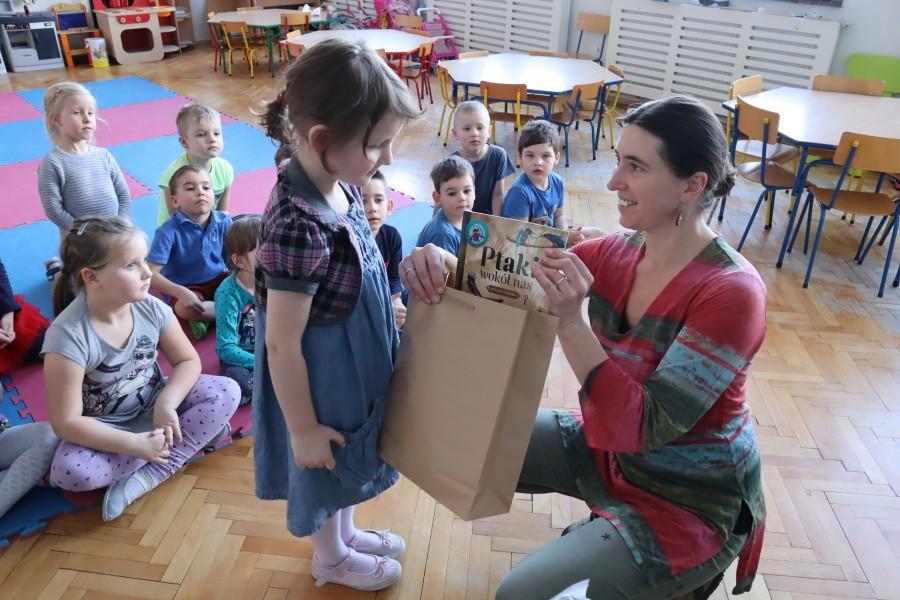 dziewczynka odbiera nagrodę zrąk nauczcielki wtle pozostałe dzieci