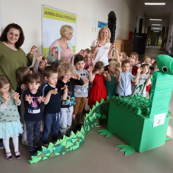 grupa przedszkolaków znauczcielkami idinozaurem zkartonów