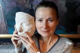 kobieta trzymająca wdłoniach maskę - odlew gliniany swojej twarzy