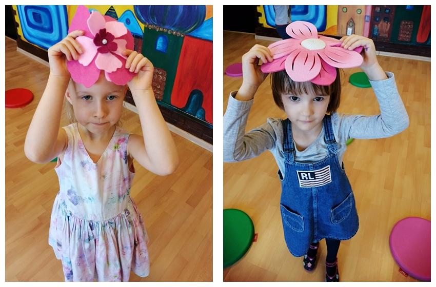 dwie dziewczynki trzmające nagłowach kwiatki
