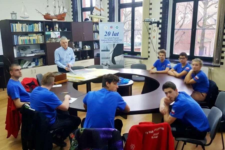 nauczyciel prowadzący zajęcia, wokół okrągłego stołu siedzą uczniowie