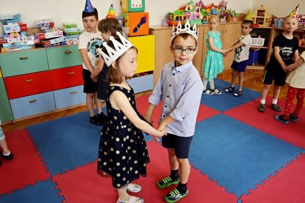 chłopiec zdziewczynką tańczą wparze, wtle inne dzieci
