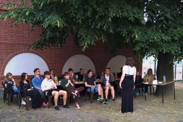grupa młodych ludzi, przednimi kobieta stojąca tyłem dofotografa