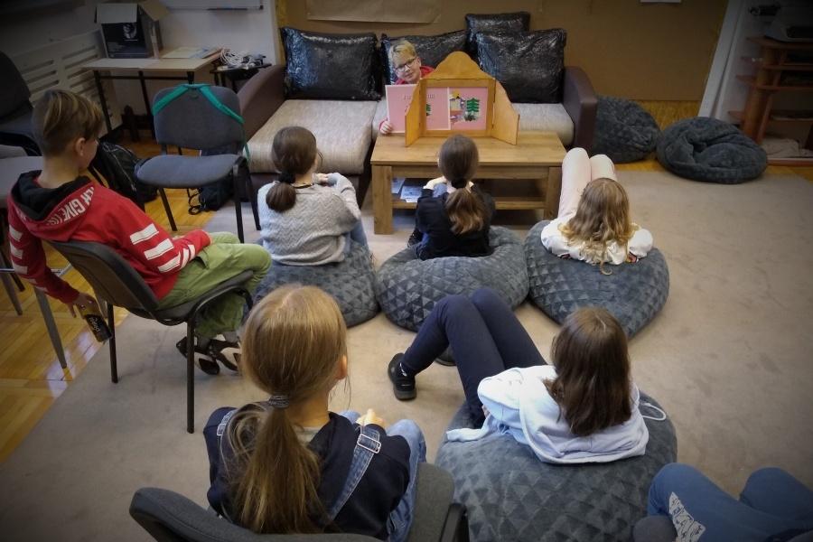 grupa dzieci siedzi i ogląda teatrzyk kamishibai