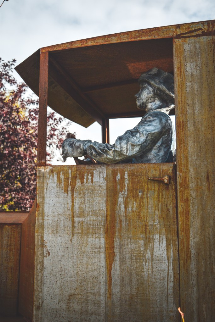 Truck sculpture by Pat Garley of a man and dog in a farm truck