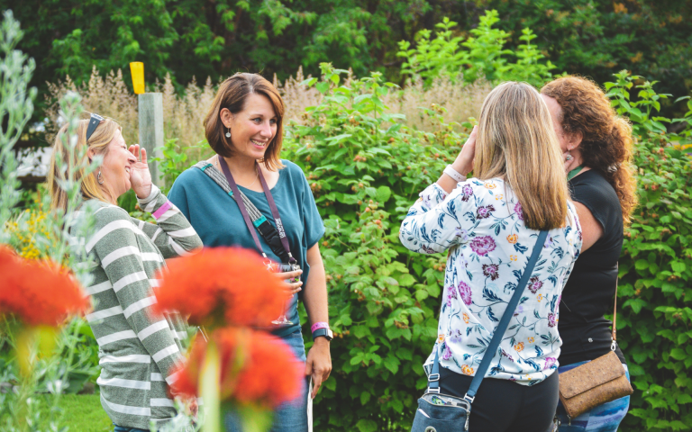 Four women touring the Showcase Garden with poppies and other flowers in bloom during the Wine Walk
