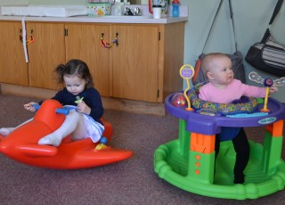 a toddler sitting on a toy airplane and a baby sitting in an exersaucer in the church's nursery