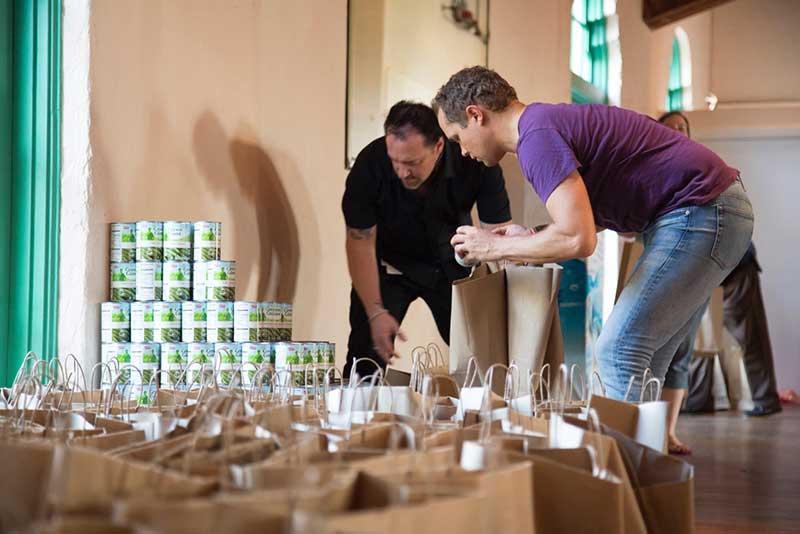 Basket Brigade volunteers filling bags with food