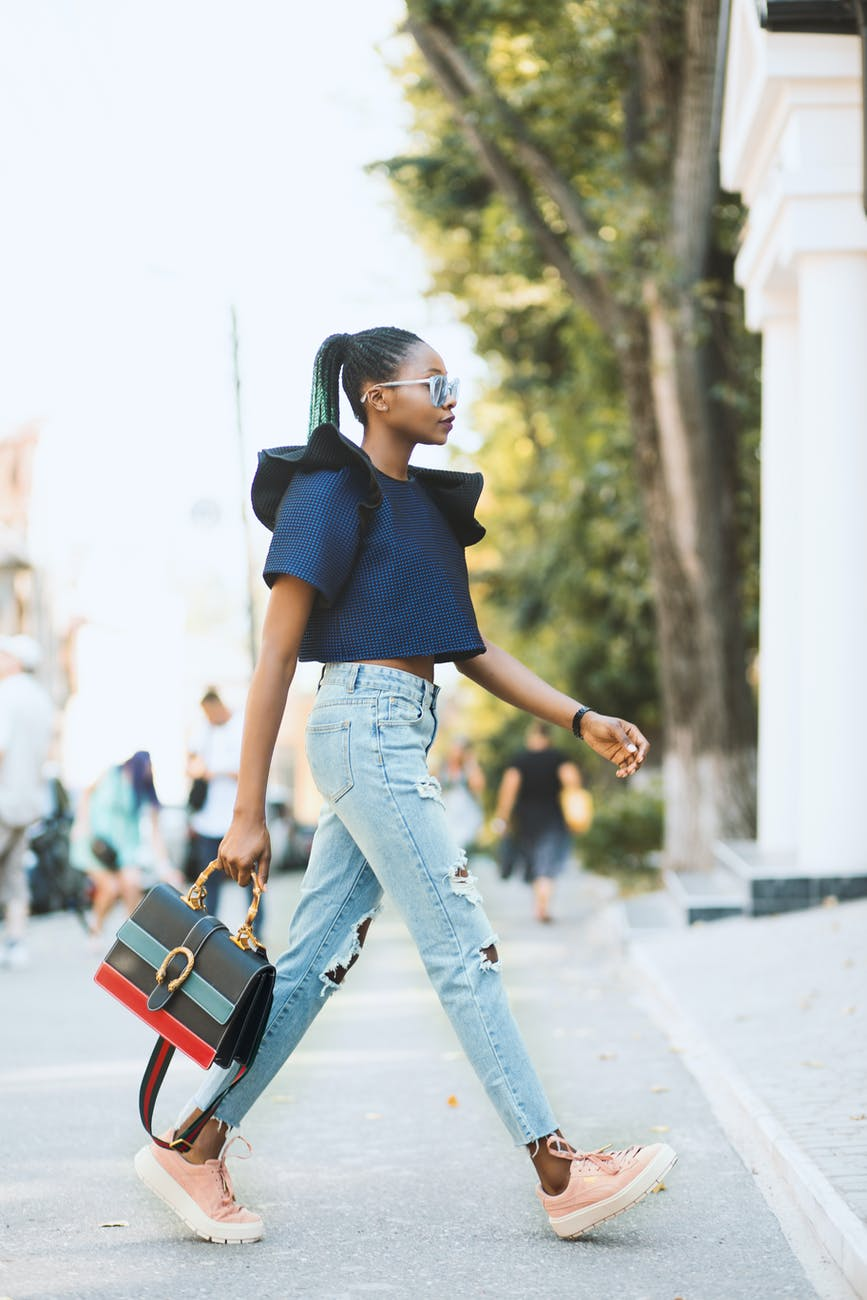 woman in blue crop top and distressed blue denim jeans holding black handbag walking on road