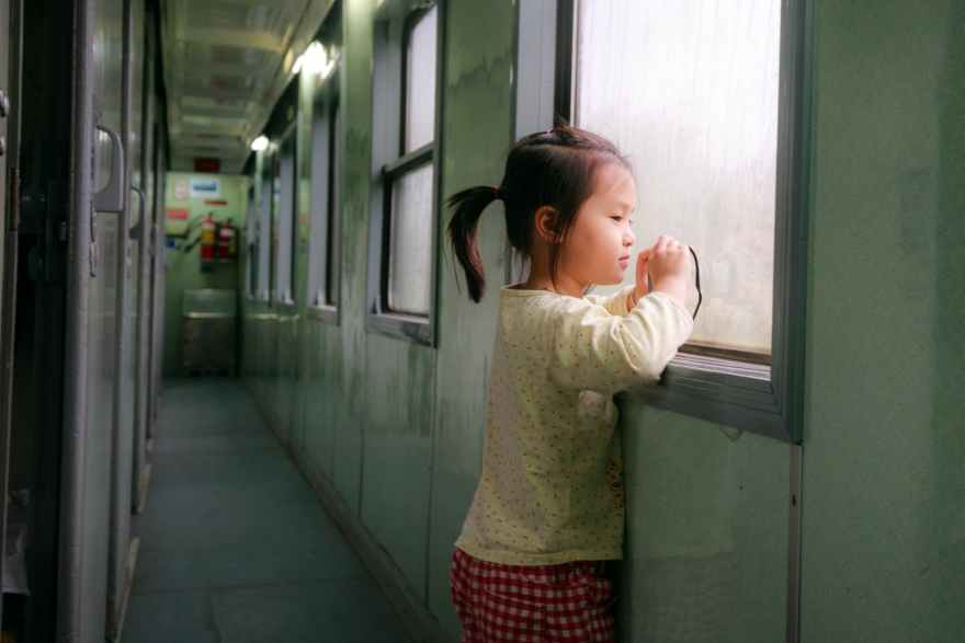 photo of girl standing by window in train hallway looking outside