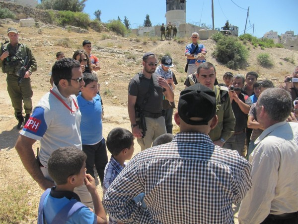 Israeli forces and Palestinian land owners arguing about the settlers tent (Photo by ISM)