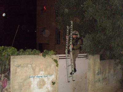 Israeli soldier climbing fence surrounding the Palestinian home. The door was unlocked the entire time (Photo by ISM)