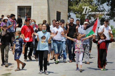 Protesters marching down the road towards the spring (Photo By Tamimi Press)