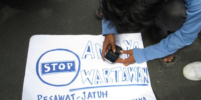 Seorang wartawan menulis pesan lewat Blacberry di atas selembar pamplet protes kekerasan terhadap jurnalis di Bundaran Hasanuddin Palu, Sulawesi Tengah, Rabu (17/10).