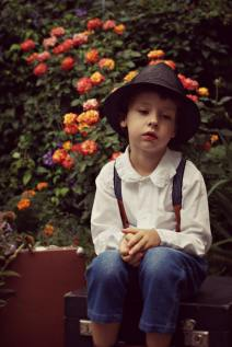 boy-wearing-black-hat-sitting-on-case-near-flowers-1049950