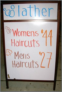 sign showing different hair cut prices for women and men