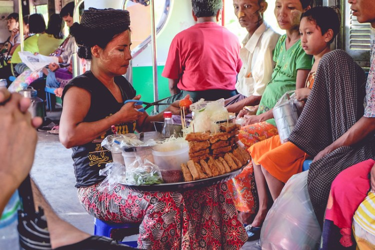 A Burmese woman sells fried tofu stuffed with chilies, a soy-based sauce, and shredded cabbage on the circle line in Yangon.