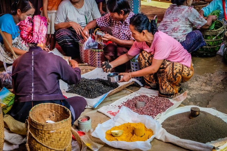 A hilltribe woman uses tin cans as a unit of measurement for locally grown tea, and various spices at the Ywa-ma market on Inle Lake.