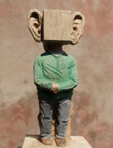 Ein stehender Mann auf Sockel vor ockerfarbenem Hintergrund. Er trägt ein grünes Hemd ind graue Hosen. Die Hände sind vor dem Buch gefaltet. Sein Kopf ist ein Würfel mit riesigen Ohren.