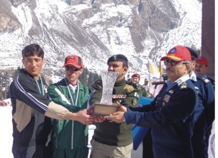 The Air Chief Marshal is handing over the winners' trophy to the Gilgit-Baltistan Scouts' team captain