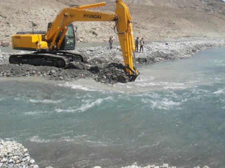 Excavator busy digging the river to divert the flow of water. Photo: Hidayat Shah