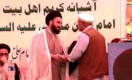 Aitmadi Fida Ali Aisar handing over a cheque to Agha Rahat
