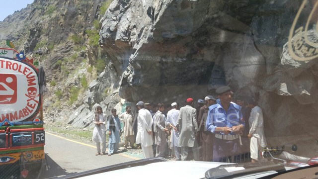 A group of locals surrounding a dead body recovered from the ravine.