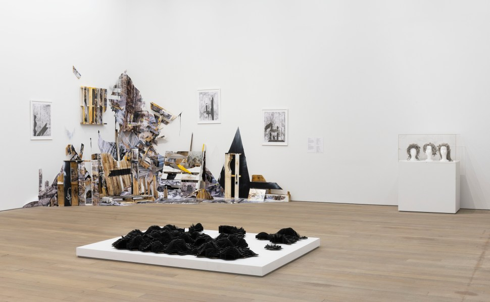 an installation view with wood and other found materials in a corner and a mound of black plastic-like material in the center