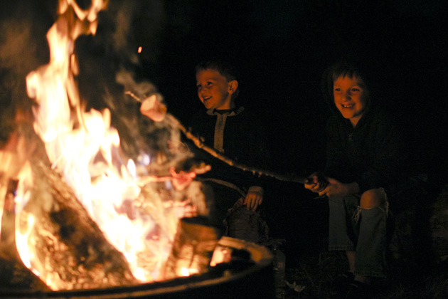 Boys roasting marshmallows at campout