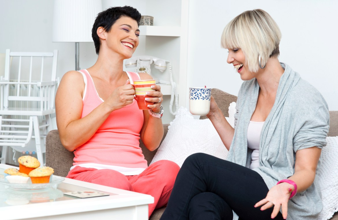 two happy ladies talking over coffee