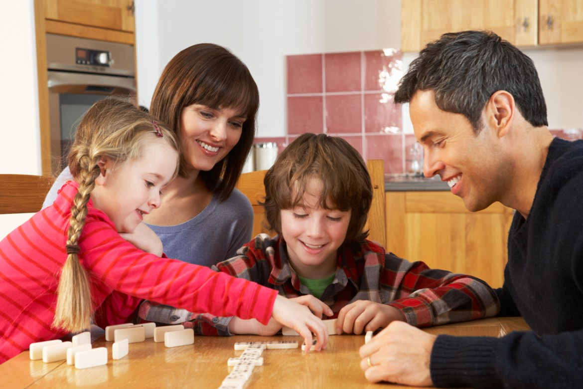 Family Playing Dominoes In Kitchen Sitting Around Having Fun