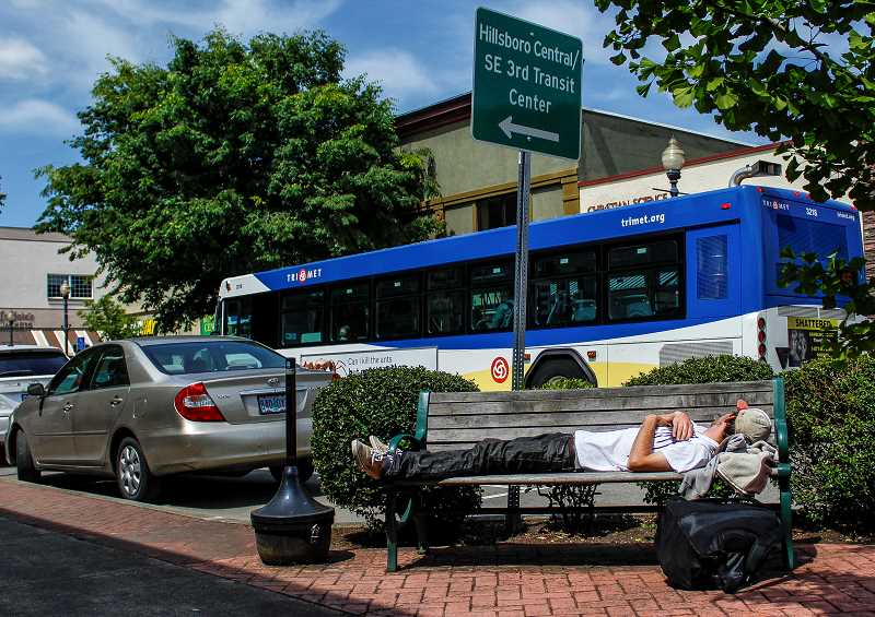 HILLSBORO TRIBUNE PHOTO: TRAVIS LOOSE - A homeless man sleeps on the bench in front of Premier Community Bank in downtown Hillsboro. Residents and business owners are encouraged to give out the lime-green Community Connect contact card to any person found panhandling or sleeping on the street.
