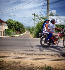 Biker duo crossing through town in Santa Elena, Cayo