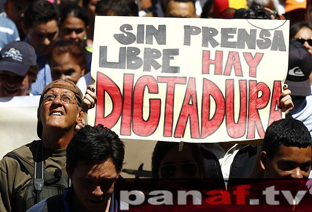 "A woman holds up a sign reading ""'Without free press, there is a dictatorship"", during a protest by newspaper workers and opposition parties to demand from the government U.S. dollars at a prime rate to buy paper for their publications, in Caracas"