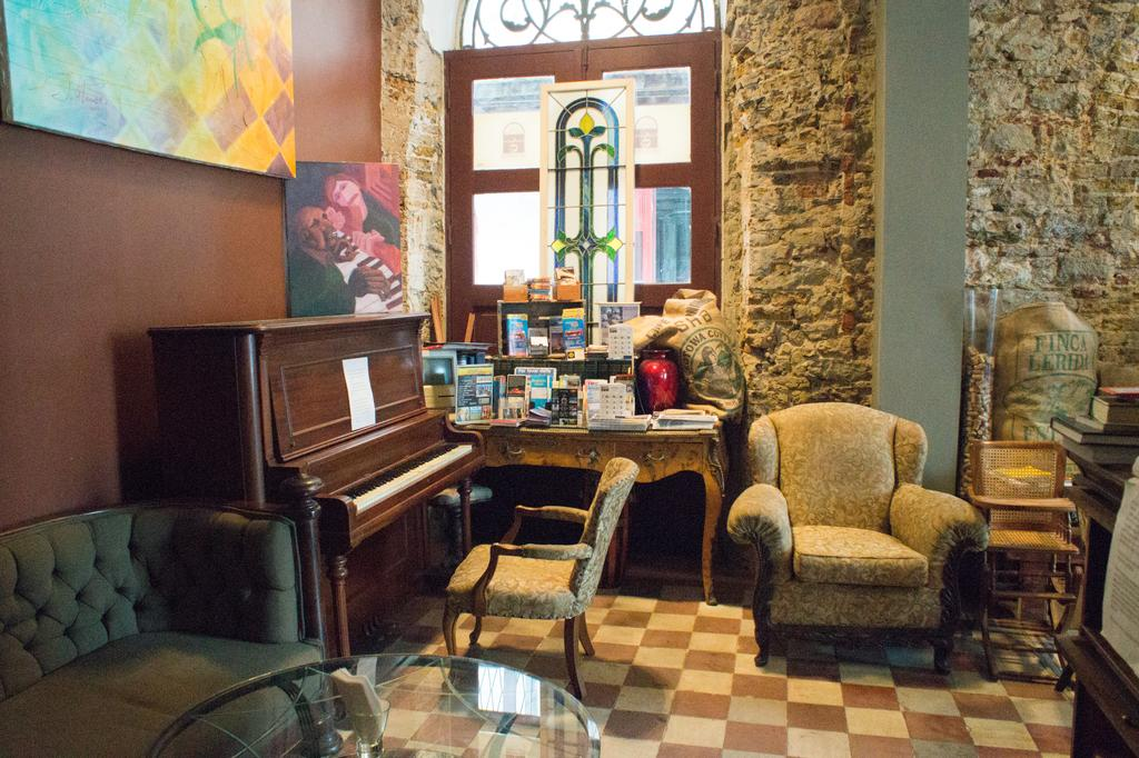 There is a piano and sofas on the corner of Casa Sucre Coffeehouse