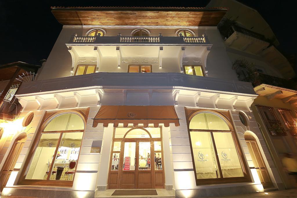 Exterior view of the Villa Palma Boutique Hotel building illuminated at night