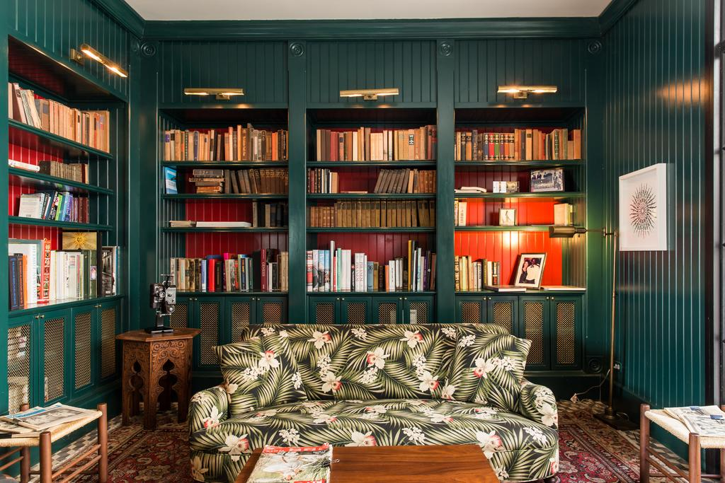 Library with books and tropical sofa in American Trade Hotel
