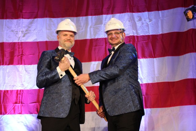 "2018 Chair of the Board, Will Cramer, ""passes the gavel"" to incoming 2019 Chair of the Board, Doug Moore, at the 2019 Annual Dinner and Awards Ceremony."