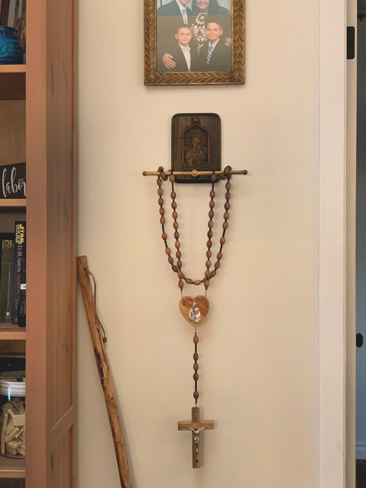 The art of risky decorating with a wall rosary holder with vintage Our Lady of Perpetual Help plaque.