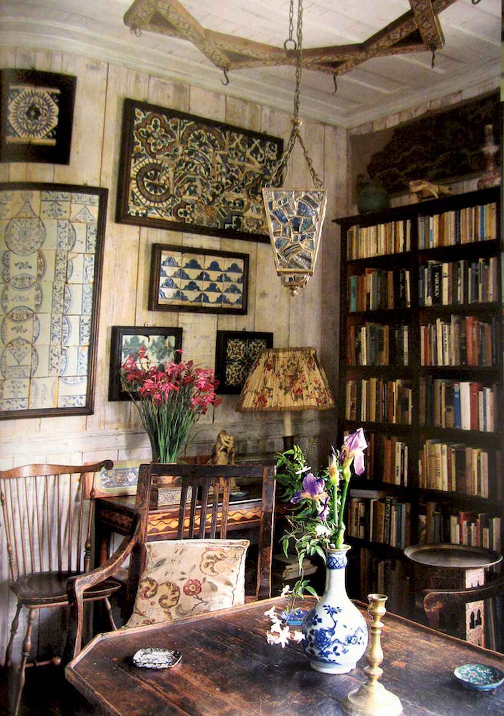 Wall of books and a crooked lamp with a pleated lampshade.