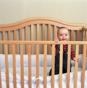Baby boy (9-12 months) standing in crib, smiling, portrait