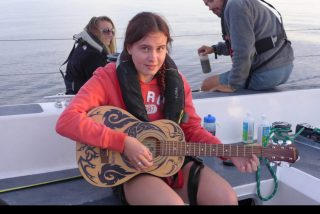 Olivia tries out Andrew's guitar on deck during one of the most beautiful sunsets imaginable!
