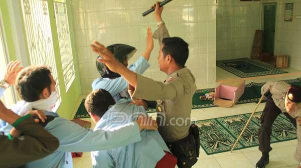 Dengan menggunakan sepatu aparat kepolisian masuk ke mushalla untuk menganiaya mahasiswa dengan brutal, sementara Al-Qur'an berserakan akibat aksi brutal aparat. Foto: JPNN