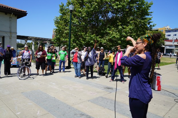Gina Madrid performing for the gathered crowd attending the Hands Around the Lake event
