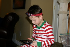 Holden with his new prized possessions. A head lamp and a Nintendo DSi.