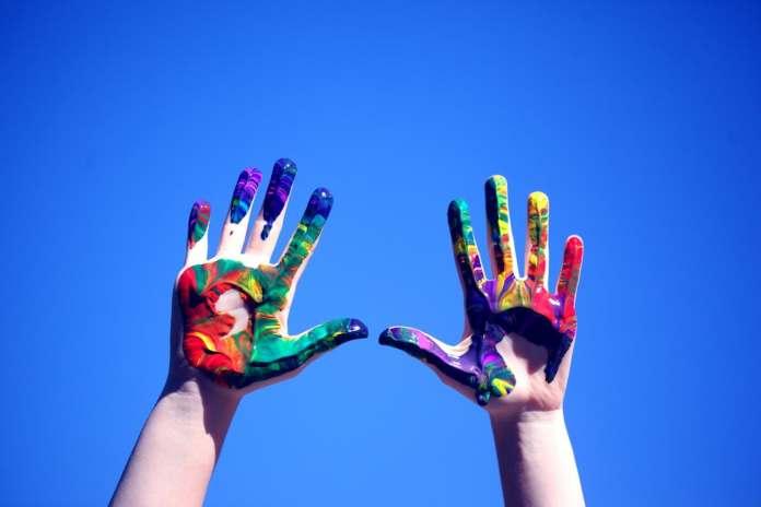 des mains d'enfants levées vers le ciel avec de la peinture : la routine de la joie, le jeu et vive la vie les enfants !