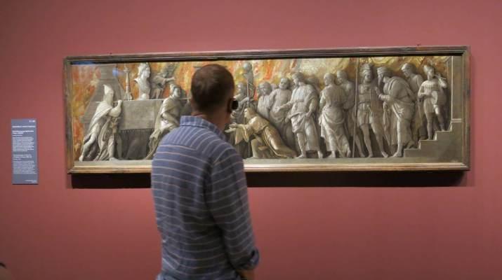 Besucher betrachtet ein Bild von Andrea Mantegna
